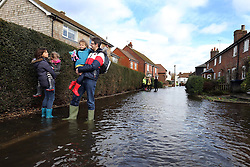 A young family struggle through a flooded street in the village of Bridge, Kent , United Kingdom. Sunday, 9th February 2014. Picture by Stephen Lock / i-Images