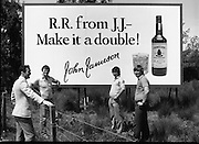 President Reagan Visits Ireland..Advertising Campaign.1984.04.06.1984.06.04.1984.4th June 1984..Availing of the opportunity of the President Reagan visit, the Whiskey manufacturers advertised their wares..Photo of advertising billboard. Was this a foretelling of the future,the words Bush and President in the same sentence..Photo shows a large billboard encouraging RR (Ronald Reagan) to have a double. Passers by discuss the billboard.. Jameson's, Irish, Whiskey, jameson,