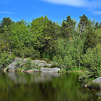 1st Stampe Lake at Baneheia Park in Kristiansand, Norway <br /> When Christian IV founded Christianssand in 1641, part of his master design was to convert a forested area into a beautiful park.  However, by the mid-19th century, most of the trees had become lumber for building homes. It was nicknamed &ldquo;Disgusting Health.&rdquo; In 1862, General Oscar Wergeland took the initiative to restore the land&rsquo;s splendor. During the next several years, his garrison soldiers planted 10,000 trees. By the turn of the century, that number had grown to over 150,000.  It is once again a beautiful place to enjoy as this woman laying on a rock can confirm.
