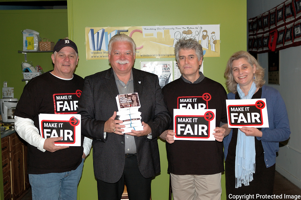 Windsor, Ontario, 2017. Left to right, John, Chrysler worker and photographer, Percy Hatfield, MPP, Paul Chislett, president, WWEC and Mereille Coral, adult education teacher, pose with FAIR signs and pamphletts in the afternoon at Windsor Workers Education Centre. FAIR is a minimum wage initiative.