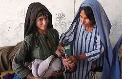GERESHK,AFGHANISTAN - SEPT. 4: A female Afghan inoculator administers the polio vaccination to the child of an internally displaced Afghan women from the Kuchi tribe on the last day of a three-day nation wide immunization campaign September 5, 2002 near Gereshk, Afghanistan.  The latest campaign targeted 5.9 million children under the age of five and teams of vaccinators went from village to village to ensure that all children in that age bracket were immunized. (Photo by Ami Vitale/Getty Images)