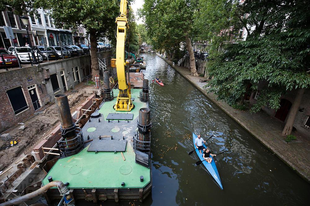 In Utrecht varen kano's langs een grote werkboot voor het herstel van de kades van de Oudegracht.<br /> <br /> In Utrecht canoes pass a boat for construction works at the quay of the Oudegracht.