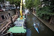In Utrecht varen kano&rsquo;s langs een grote werkboot voor het herstel van de kades van de Oudegracht.<br /> <br /> In Utrecht canoes pass a boat for construction works at the quay of the Oudegracht.
