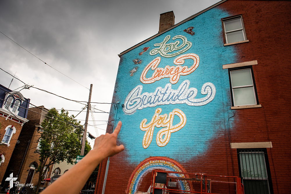 Artist Rachel Ziegler points to a new mural adorning the side of Victoria's House of Hope, a transitional housing apartment building that is part of The Welcome Home Collaborative program, on Wednesday, May 16, 2018, in Cincinnati. Victoria, a young woman who volunteered her time at Prince of Peace Lutheran Church in the Over-the-Rhine neighborhood of Cincinnati, made a wish to the Make-a-Wish Foundation to rehab the old building before she died of a brain tumor. Ziegler designed the mural and had attendees of the church and external community assist with the construction. LCMS Communications/Erik M. Lunsford