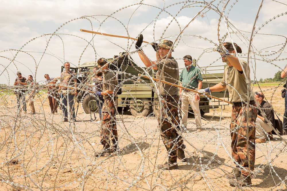 Hungarian military begin work on controversial barrier fence to halt refugee movement from Serbia.