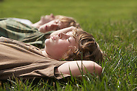 Three teenage brothers (13-17) lying down on grass close up