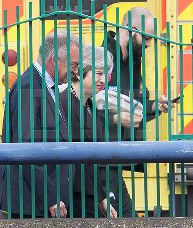 © Licensed to London News Pictures. 15/03/2018. Salisbury, UK. British Prime Minister THERESA MAY walks past an ambulance as she visits Salisbury District Hospital, Wiltshire where Former Russian spy Sergei Skripal and his daughter Yulia are being treated after being poisoned with nerve agent. The couple where found unconscious on bench in Salisbury shopping centre. A policeman who went to their aid is currently recovering in hospital. Photo credit: Peter Macdiarmid/LNP