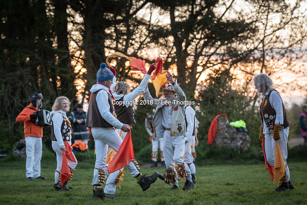 Rollright Stones, Nr Long Compton, Oxfordshire / Warwickshire, UK. 1st May 2018.  Members of the Owlswick Morris side entertain spectators at sunrise with traditional dancing at the historic Rollright Stones to celebrate the 1st May.  The Rollright Stones is a complex comprising of three Neolithic and Bronze Age megalithic monuments near the village of Long Compton, on the borders of Oxfordshire and Warwickshire. Made from local oolitic limestone, the three monuments now known as the King's Men and the Whispering Knights in Oxfordshire and the King Stone in Warwickshire, were built at separate periods in late prehistory.  // Pictured: The Owlswick Morris side dance inside the King's Men stones at dawn. / Lee Thomas, Tel. 07784142973. Email: leepthomas@gmail.com  www.leept.co.uk (0000635435)