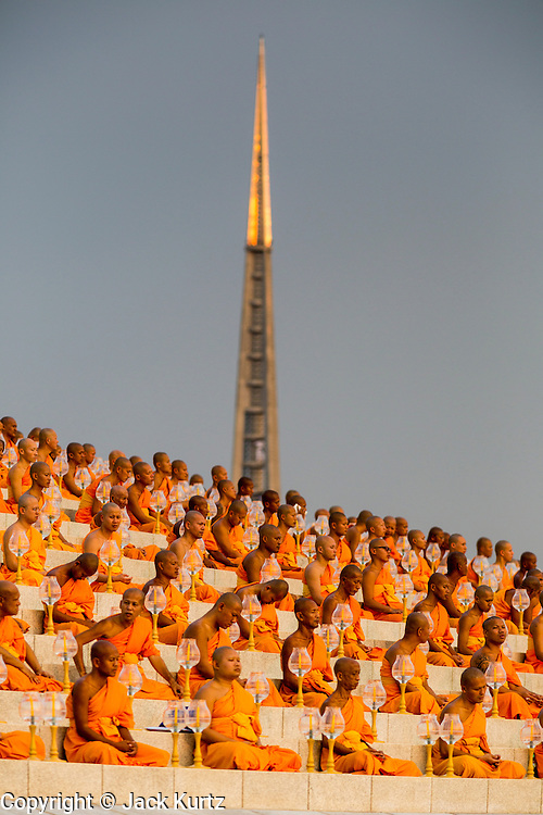 """14 FEBRUARY 2014 - KHLONG LUANG, PATHUM THANI, THAILAND: Buddhist monks sit around the Maha Dhammakaya Cetiya during Makha Bucha Day at Wat Phra Dhammakaya.  The aims of Makha Bucha Day are: not to commit any kind of sins, do only good and purify one's mind. It is a public holiday in Cambodia, Laos, Myanmar and Thailand. Many people go to the temple to perform merit-making activities on Makha Bucha Day. The day marks four important events in Buddhism, which happened nine months after the Enlightenment of the Buddha in northern India; 1,250 disciples came to see the Buddha that evening without being summoned, all of them were Arhantas, Enlightened Ones, and all were ordained by the Buddha himself. The Buddha gave those Arhantas the principles of Buddhism, called """"The ovadhapatimokha"""". Those principles are:  1) To cease from all evil, 2) To do what is good, 3) To cleanse one's mind. The Buddha delivered an important sermon on that day which laid down the principles of the Buddhist teachings. In Thailand, this teaching has been dubbed the """"Heart of Buddhism."""" Wat Phra Dhammakaya is the center of the Dhammakaya Movement, a Buddhist sect founded in the 1970s and led by Phra Dhammachayo.    PHOTO BY JACK KURTZ"""