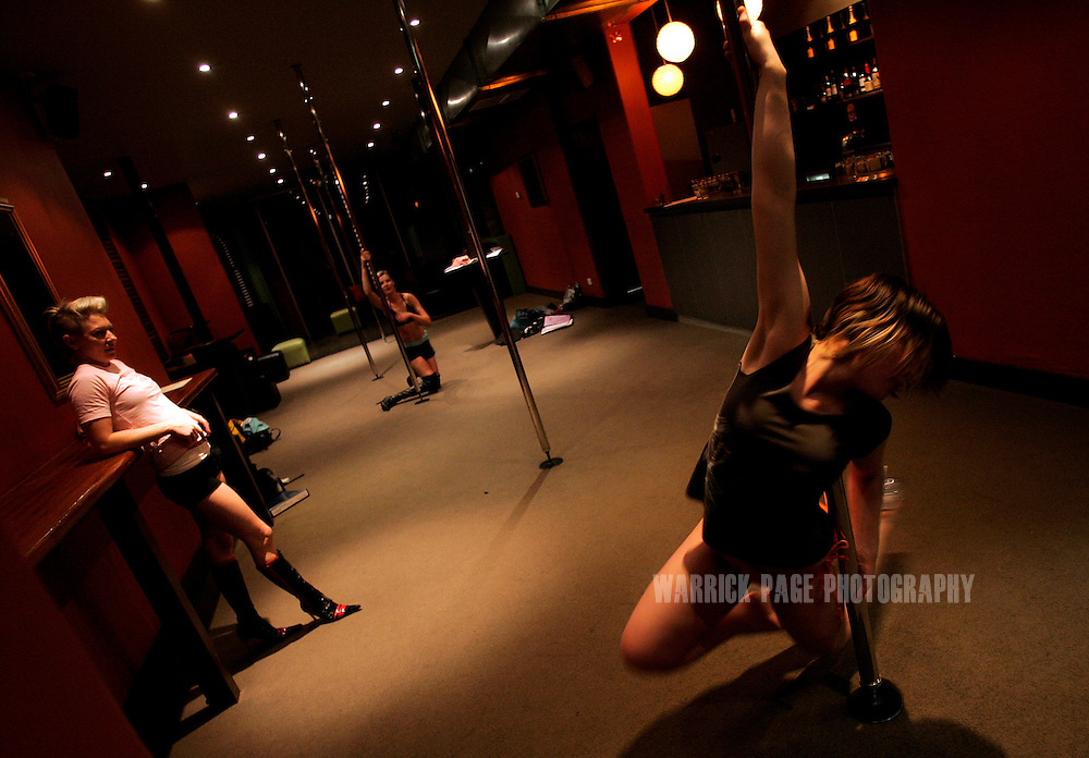 "MELBOURNE, AUSTRALIA - AUGUST 7: Lauren Rui (R), 18, a university student, performs a move while instructor Andi (L), 33, and Madeline Sinclair (C), 32, watch during an advanced pole dancing class at the Imperial Hotel, August 7, 2006, Melbourne, Australia. Lauren was introduced to pole dancing by her boyfriend, who ""recorded a television show on [pole dancing] and encouraged me to take it up"". Previously reserved for strip clubs, pole dancing is now quickly becoming a new fitness crazy throughout Australia, Europe and the US with thousands of women from all walks of life leaving traditional gymnasiums for the more social and challenging art of pole dancing. Pole dancing for fitness exploded onto the public scene after celebrities such as Angelina Jolie, Jennifer Anniston and Britney Spears professed it was their favourite form of exercise. Classes are often small in numbers giving a more personal atmosphere and strong bonds of friendship are often formed between students and instructors. Instructors claim a noticeable increase in their students' self-confidence after only a few weeks. Most students claim even thought it's a rigorous workout, they're having so much fun it doesn't feel like exercise at all. According to ""Polestars"", a British company that began setting up classes throughout six Australian cities in 2004,  ""a good session on the pole"" can burn more calories than at the gym and provide more muscle tone. (Photo by Warrick Page)"