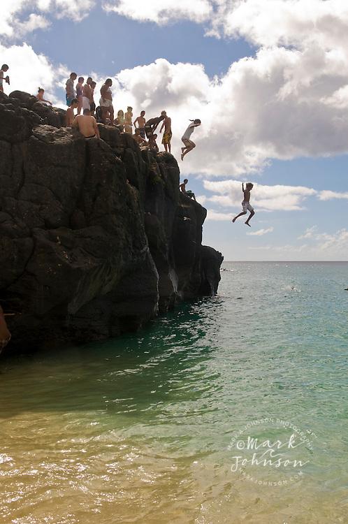 Young people jumping off rock into sea at Waimea Bay, Oahu, Hawaii