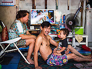 "08 FEBRUARY 2017 - BANGKOK, THAILAND: A family that makes artisan bird cages relax with their son in their home in Pom Mahakan. The residents of the old fort are known for their community of song bird enthusiasts. More than 40 families still live in Pom Mahakan, a slum community in a 19th century fort in Bangkok. City officials are trying to move them out of the fort but members of the community refuse to leave. NGOs and historic preservation organizations are working with the community to help them find a way to stay. After several deadlines passed, residents were told that they have to leave by the end of February. They submitted another proposal to the city this week to turn their community into a ""living heritage museum"" and hope to get the eviction deadline extended until late March.       PHOTO BY JACK KURTZ"