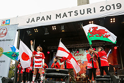"© Licensed to London News Pictures. 29/09/2019. London, UK. Performers performs a ""Rugby World Cup"" dance waving flags of Japan, England, Scotland and Wales during the annual Japan Matsuri festival of Japanese music, food and culture in Trafalgar Square. The concept of the theme this year is ""Future generations"". Photo credit: Dinendra Haria/LNP"