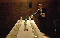 1991, Barcelona, Spain --- Waiter Pours Wine at Wine Tasting --- Image by © Owen Franken/CORBIS