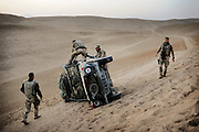 During a patrol a, german wolf flipped over causing minor injuries to the crew. an hour later the car was turned over again and transported back to the PRT in Faizabad.<br /> German soldiers helping fellow soldiers who tipped over with their WOLF 4x4 in the mountains in the desert some 50 km. from Faizabad in northern Afghanistan. <br /> For more caption info, please contact photographer.