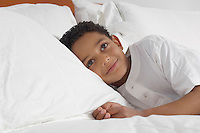Boy (7-9) lying in bed smiling, portrait