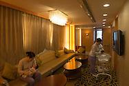 Shanghai, 21 septembre 2012.Dans un salon de la clinique  VIP Care Bay specialisee dans les soins post-natals, deux infirmières s'occupent des bebes de leur cliente pendant que ces dernières se reposent. Chacune des ces infirmières sont dédiées a une seule maman pour laquelle elles sont disponibles 24h sur 24, 7 jours sur 7 pendant toute la durée du séjour, généralement 1 mois..