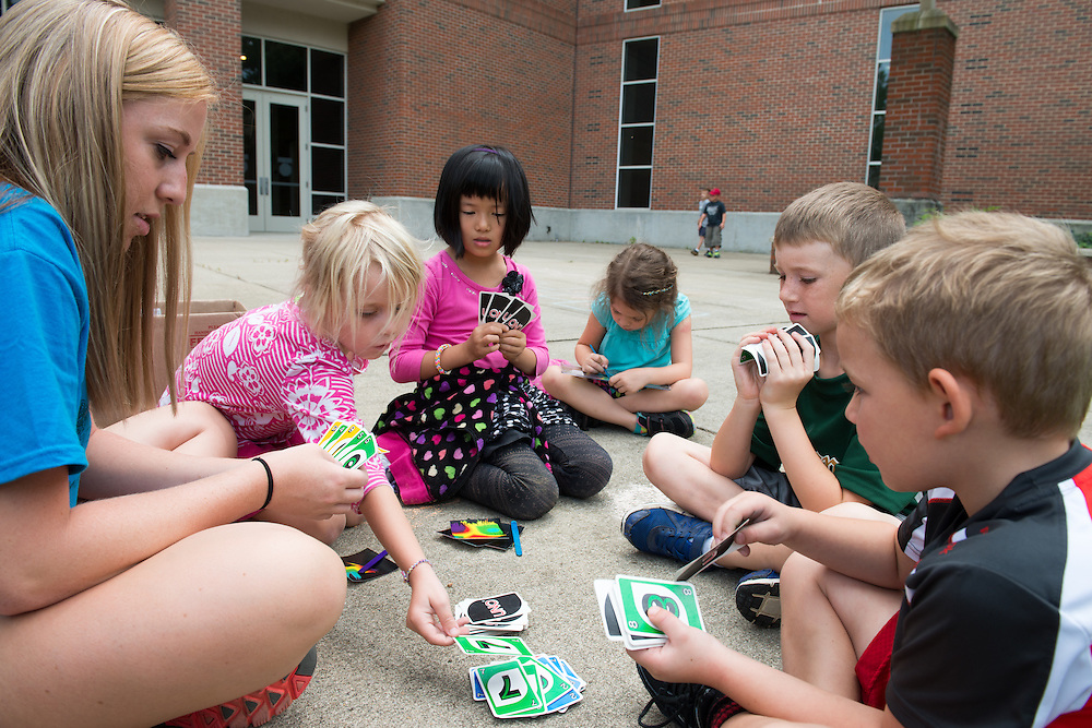 Campus Recreation day campers play Uno and draw with Camp Counselor Sarah Andrews (Let) outside of Ping. Photo by Ben Siegel/ Ohio University