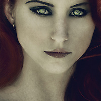 Close up portrait of a girl with red hair and piercing eyes