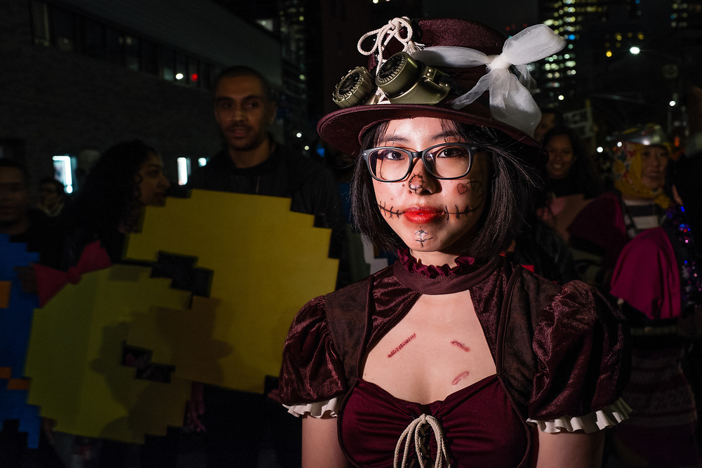 New York, NY - 31 October 2019. the annual Greenwich Village Halloween Parade along Manhattan's 6th Avenue. A woman in a deep plum velvet dress and steampunk goggles bears scars on her chest.