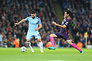 Barcelona midfielder Sergio Busquets attempts a sliding tackle on Sergio Agüero of Manchester City during the Champions League match between Manchester City and Barcelona at the Etihad Stadium, Manchester, England on 1 November 2016. Photo by Simon Brady.