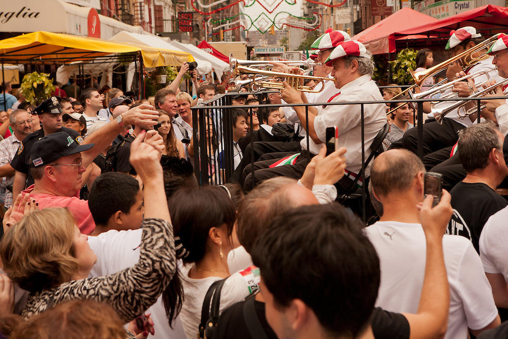 New York, NY -24 September 2011. The feast of San Gennaro in New York's Little Italy. The band surrounded by bystanders as it goes down Mulberry Street.