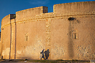 A man walking along city wall in old town, Essaouira, Morocco in late day light.