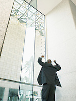 Businessman with arms raised in office building