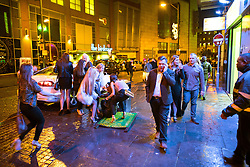 """© Licensed to London News Pictures . 17/12/2016 . Manchester , UK . A woman stumbles over an A board on Withy Grove . Revellers out in Manchester City Centre overnight during """" Mad Friday """" , named for being one of the busiest nights of the year for the emergency services in the UK . Photo credit : Joel Goodman/LNP"""