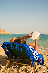 man reading while on a lounge chair in Mykonos, Greece