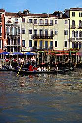 Venice, Italy: A gondola load of tourists surveys the Rialto area of the Grand Canal.