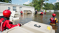 Team members from the HSUS Animal Rescue Team (ART), acting on a pet owners request, seek to enter a locked house trailer in an effort to rescue the pet they were told was inside. The area was forced to evacuate suddenly after  catastrophic flooding due to Hurricane Harvey ravaged Beaumont along with other Texas coastal regions. <br />