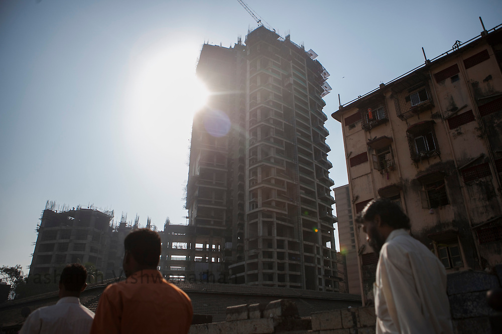 Men walk past an under construction, multistoried residential apartment complex in Mumbai, Maharashtra, India, February 28, 2012. Photographer: Prashanth Vishwanathan
