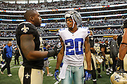 Dallas Cowboys cornerback Michael Coe (20) and New Orleans Saints linebacker Ramon Humber (53) talk after the New Orleans Saints beat the Dallas Cowboys in overtime, 34-31, at Cowboys Stadium in Arlington, Texas, on December 23, 2012.  (Stan Olszewski/The Dallas Morning News)