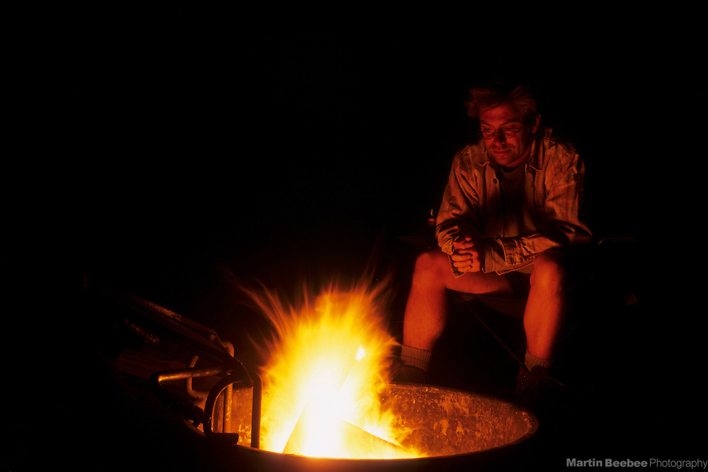 Man sitting in front of campfire, Coronado National Forest, Arizona
