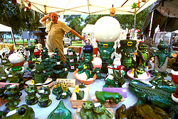 Stock photo of a vendor striking a pose behind his wares at the Anhuac Texas Gatorfest