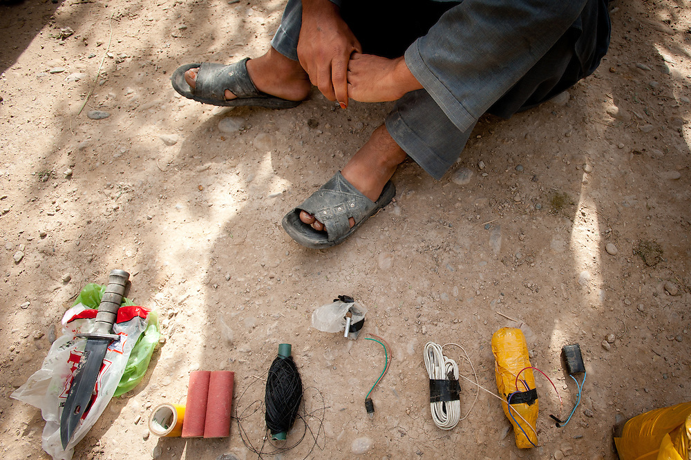 Various materials used to build and emplace improvised explosive devices are laid out in front of a suspected Taliban fighter: kite strings for detonating the device, a plastic jug, a battery, and a bag of homemade explosives.