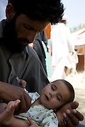 A father and his 8 month old son at Shaik Yaseen IDP Camp...Residents from SWAT valley begin arriving at Shaik Yaseen IDP camp at outside of Mardan in North West Frontier Province, Pakistan...More than 1400 families have reportedly registered as IDP's seeking shelter and food at the hastily arranged camp. According to UNHCR Some 500,000 residents have fled SWAT and neighboring provinces since August 2008. Last Thursday the Pakistan Government announced a military operation to 'eliminate' Taliban militants form the SWAT Valley. A further 1 million IDp are expected in the coming weeks as the military advances throughout SWAT valley towards achieving their military goals...