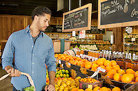 Handsome young man shopping for fruits in market