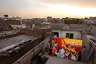LAHORE, PAKISTAN - MAY 11: Billboard painter, Muhammed Ajmal (R), and his workers move a work-in-progress indoors as dusk settles over the city on Friday, May 11, 2007, in Lahore, Pakistan. Billboard painters have had to cut their prices in half due to few Lollywood productions and the use of soft-porn posters to entice patrons. As thawing relations between Pakistan and India lead them closer to regional stability, Pakistan's film industry takes another hit as Bollywood films dominate an already floundering institution, as the Pakistani government eases a 43-year-old ban on screening Indian films and audiences are drawn to their neighbours silver-screen theatrics. Once a thriving film industry in the chaotic and colourful city of Lahore, Pakistan's answer to Bollywood - Lollywood - is now a shadow of its former self. Two decades ago 11 studios averaged a collective 100+ films per year as cinemagoers filled more than 1000 theatres across the country. Today, only one functioning studio struggles to produce a single film for the country's 200 decaying theatres. (Photo by Warrick Page)