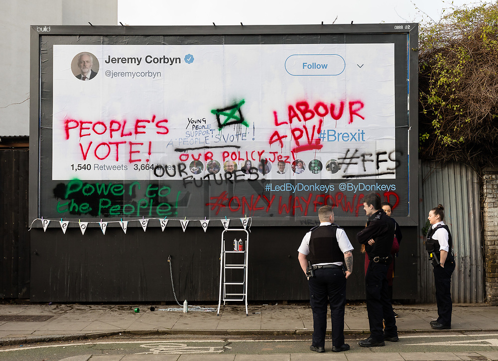 © Licensed to London News Pictures. 12/02/2019. London, UK.  Passing police officers stop to look at young anti-Brexit campaigners from the For our Future's Sake (FFS) wing of the People's Vote campaign in collaboration with the Led By Donkeys campaign writing messages on a large billboard in Islington, stating why they want Jeremy Corbyn, the leader of the Labour Party to back a People's Vote on Brexit. The billboard, located in the Islington North constituency of Mr Corbyn shows messages reminding him that a majority of young Labour supporters want a public vote or second referendum on Brexit. Photo credit: Vickie Flores/LNP