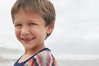 Smiling boy (5-6) on beach portrait