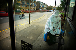 Cyclist passes women at a bus stop dressed in traditional Somali clothing, Malabar Road, St Matthew's Estate, Leicester, England, UK.