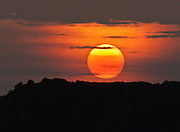 """The orange sun sets in the Galápagos Islands, Ecuador, South America. In 1959, Ecuador declared 97% of the land area of the Galápagos Islands to be Galápagos National Park, which UNESCO registered as a World Heritage Site in 1978. Ecuador created the Galápagos Marine Reserve in 1998, which UNESCO appended in 2001. Published in Martin Dawe Design company calendar 2013, UK. Published in """"Light Travel: Photography on the Go"""" book by Tom Dempsey 2009, 2010."""