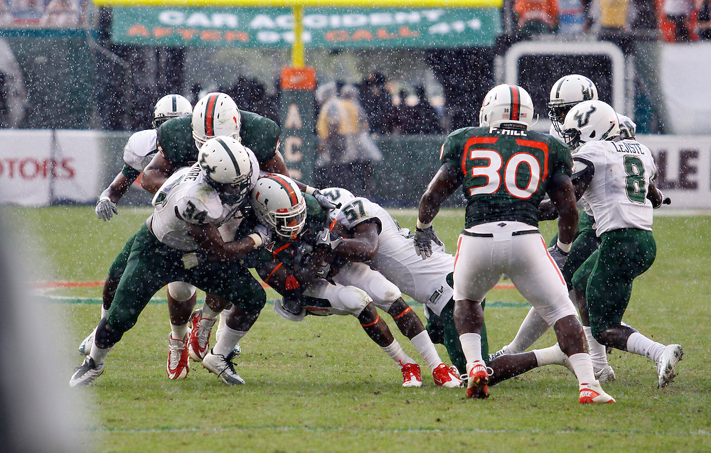 MIAMI GARDENS, FL - NOVEMBER 27: DeDe Lattimore #34 and Jacquain Williams #57 tackle Graig Cooper #2 of the Miami Hurricanes during the game against the Miami Hurricanes at Sun Life Stadium in Miami Gardens, Florida on November 27, 2010. South Florida defeated the Hurricanes 23-20.