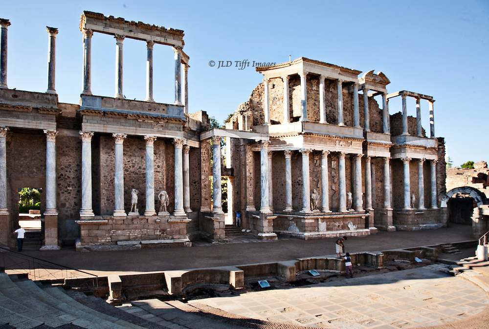 Rebuilt two storey skena or scene or scaena frons building of the Roman theater at Merida, built 16-15 BC by Vipsanius Agrippa, then consul.  White marble columns stand out in front of a rubble masonry and brick wall behind them.