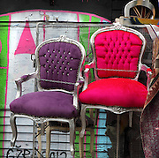 Brightly coloured chairs hanging on railings in Brick Lane area, London, UK. Picture by Manuel Cohen
