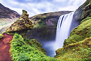 Skógafoss is a 25 m widt and 60 m high waterfall, around 5 km west of Skógar and south of Eyjafjallajökull on South-Iceland. The waterfall, which is one of the most beautiful, was protrcted in 1987. A legend says that the settler Þrasi Þórólfsson hid a gold coffin behind the waterfall | Skógafoss er et 25 m bredt og 60 m høgt fossefall ca. 5 km vest for Skógar og sør for Eyjafjallajökull på Sør-Island. Fossen som er en av Islands vakreste, ble fredet i 1987. Sagnet sier at landnåmsmannen Þrasi Þórólfsson gjemte en gullkiste bak fossen.