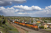 With three GE locomotives up front, and two more shoving the rear, a 100 car plus long unit ethanol train slowly grinds up the eastern slope of the Arizona Divide as it battles towards the 7,300' high summit. In the background, downtown Flagstaff can be seen; home to many bars and historic buildings that make this mountain college town spectacular. May 15, 2017