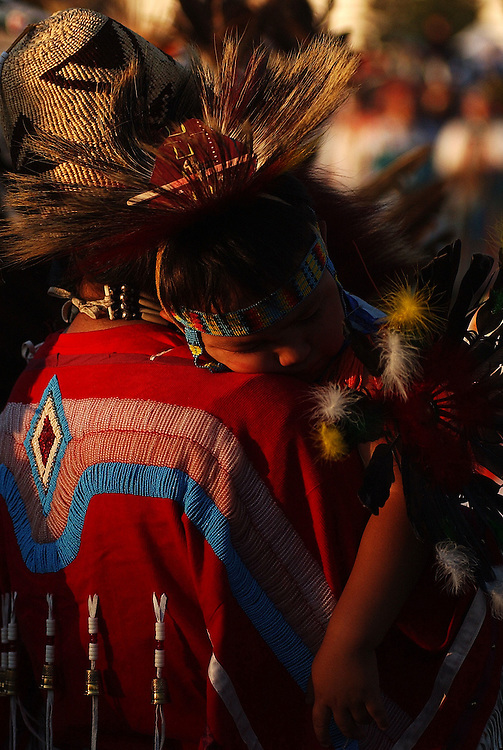 POST FALLS, ID - JULY 23:  Isaac SiJohn, 2, of the Coeur d'Alene Tribe, sleeps on his mother's shoulder during the grand entry of the Julyamsh Pow Wow in Post Falls, Idaho on Friday. The Julyamsh is touted as the largest pow wow in the Northwest.  (Photo by Jerome Pollos/Getty Images)